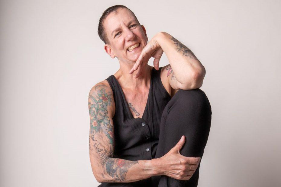 Sabine Scholze mit auf der Hand aufgestütztem Kopf, die andere Hand umfasst den Unterschenkel