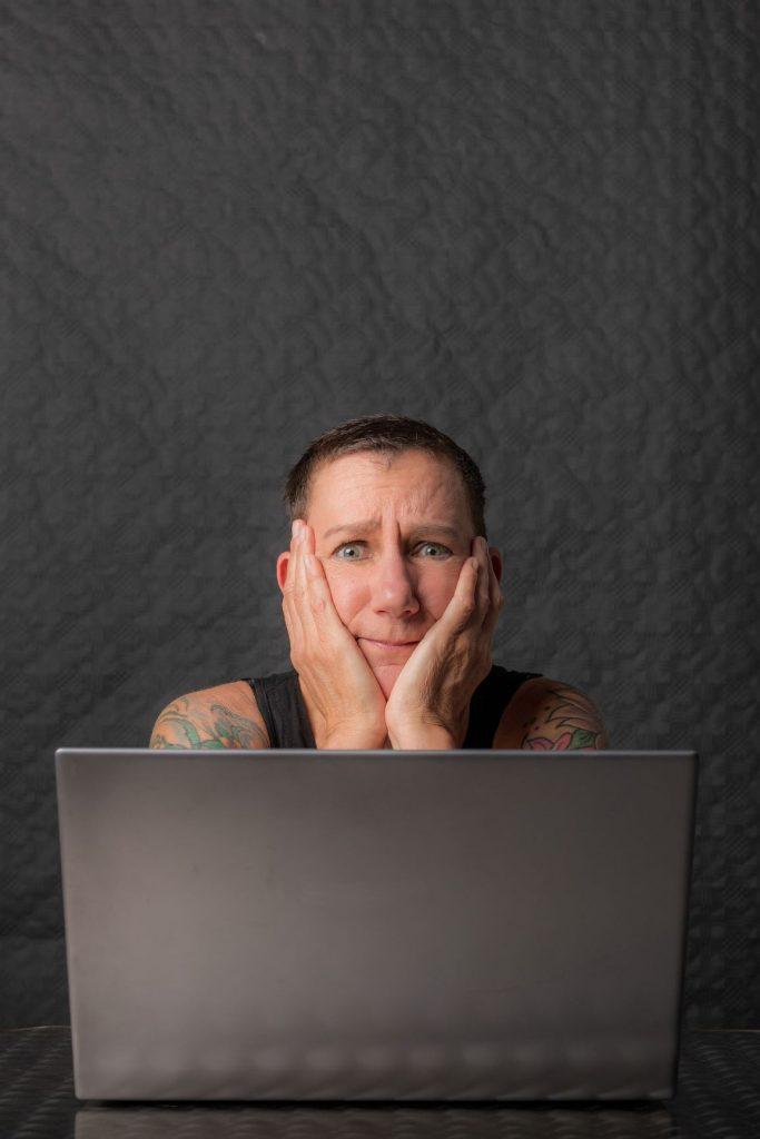 Sabine Scholze sitzt mit besorgtem Gesichtsausdruck vor einem Laptop und hat den Kopf auf die Hände gestützt. Dieser Gesichtsausdruck symbolisiert das Gefühl, nicht gut genug zu sein bzw. gearbeitet zu haben.
