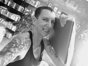 Sabine Scholze hat ihren Laptop im Arm. Im Hintergrund ist ein gut gefülltes Bücherregal zu sehen.