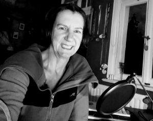 Sabine Scholze sitzt mit Kopfhörern und Mikrofon an ihrem Schreibtisch und lächelt.