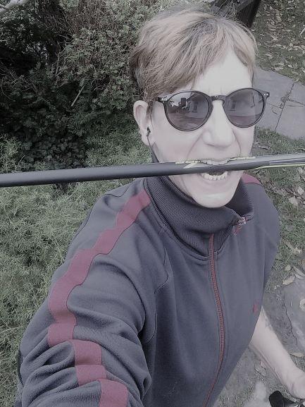 Sabine Scholze hat einen Stock zwischen den Zähnen und eine Sonnenbrille auf.