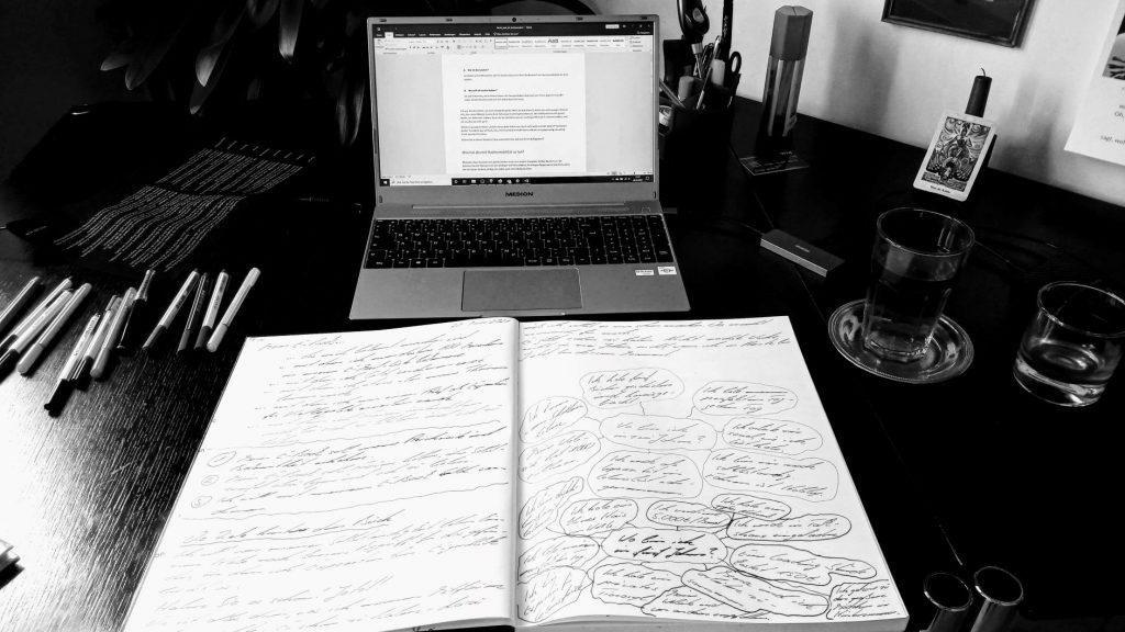 Ein aufgeklappter Laptop, davor ein Buch mit handgeschriebenen Notizen. Links daneben Stifte, rechts daneben zwei Gläser.