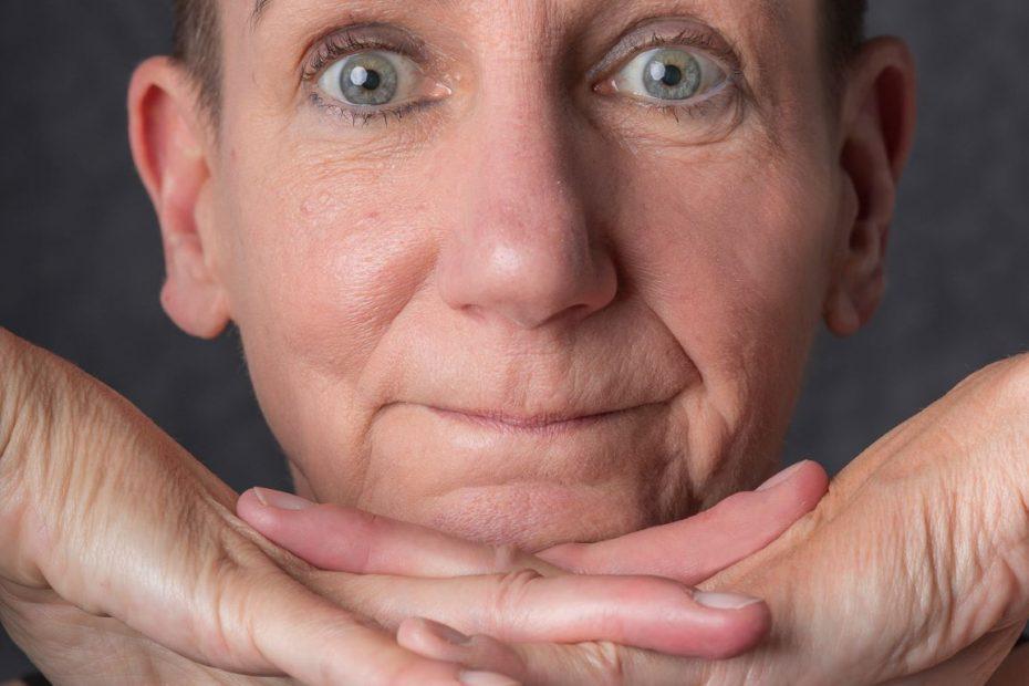 Sabine Scholze hat ihr Kinn auf den zusammengelegten Händen abgestützt und guckt fragend. Dieser Gesichtsausdruck könnte Hochsensibilität bedeuten.