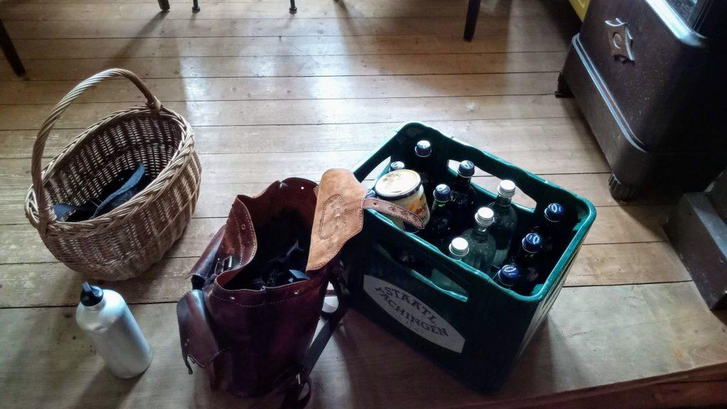 Ein Weidenkorb, ein Lederrucksack, eine SIGG-Flasche und eine Kiste Fachinger mit einem Honigglas darin.