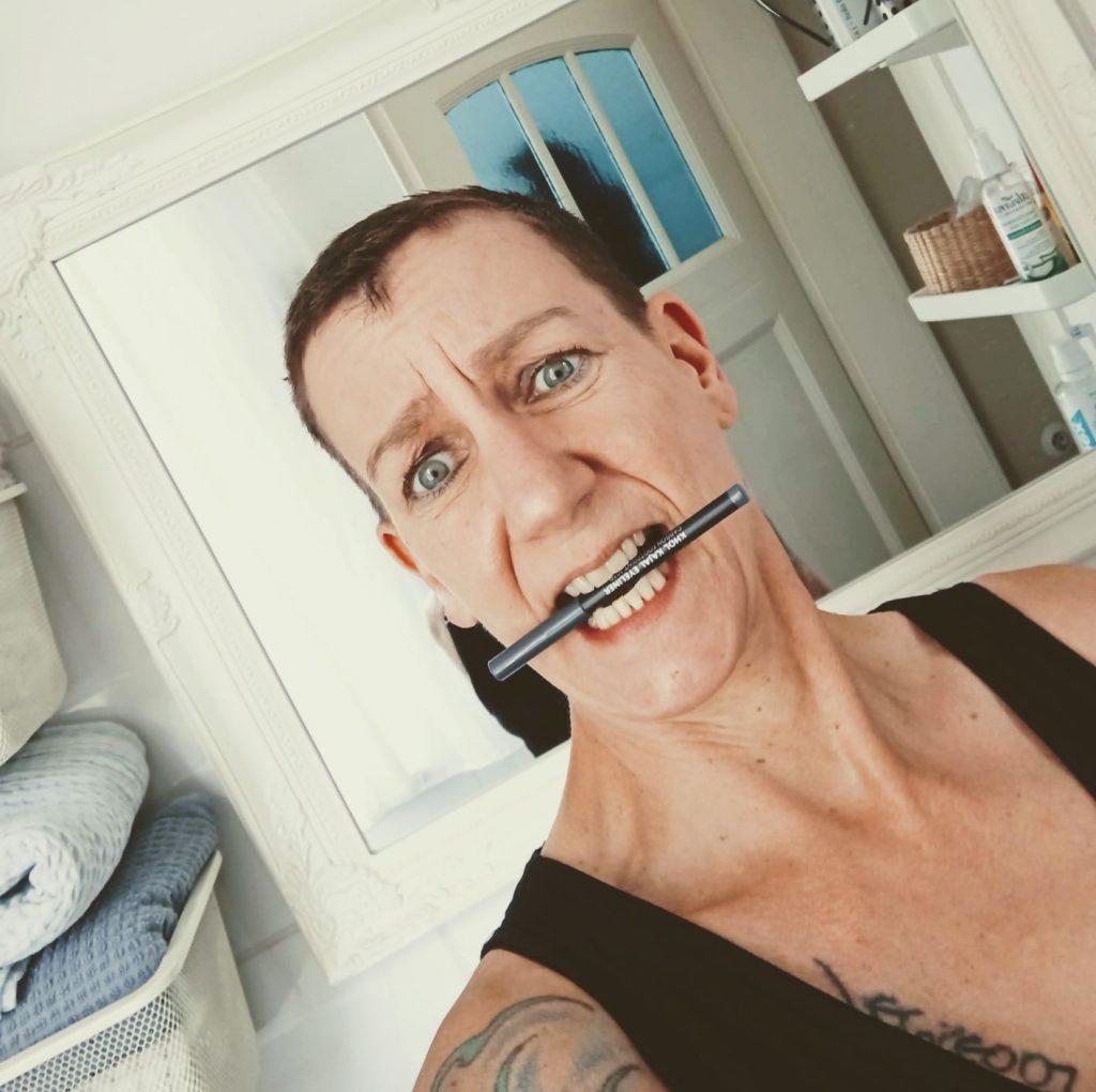 Sabine Scholze vor einem Spiegel mit einem Schminkstift zwischen den Zähnen.