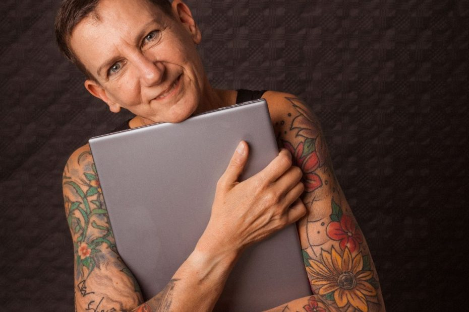 Sabine Scholze hält einen Laptop im Arm und lächelt.