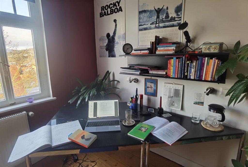 So sieht mein Schreibtisch aus, wenn ich im Home Office bin: Notizbücher, eine Menge Fachliteratur, ein aufgeklappter Laptop, ein Fenster mit schönem Blick nach draußen und Rocky Balboa an der Wand.