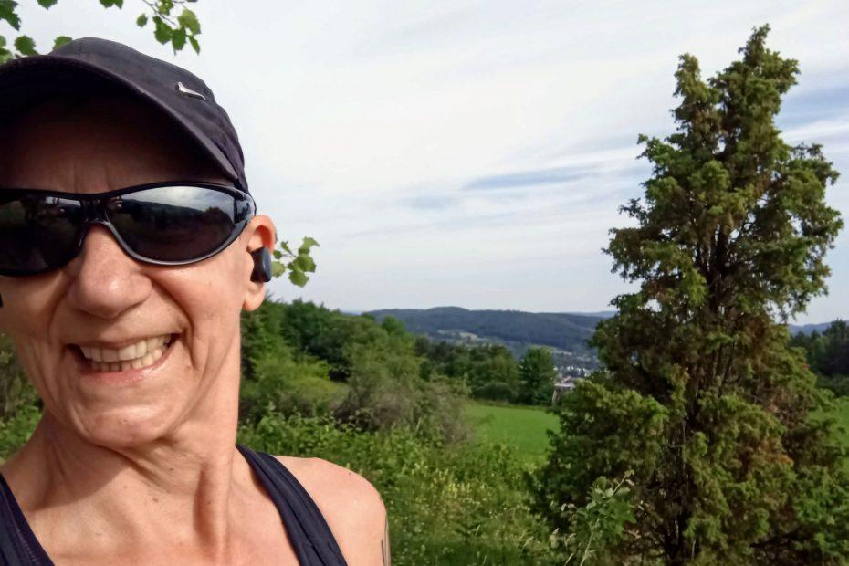 Sabine Scholze mit Sonnenbrille und Cap vor dem Hintergrund des Kaufunger Waldes - Bestandteil ihres Rückblick am 30. Juni 2021 auf das erste Halbjahr.