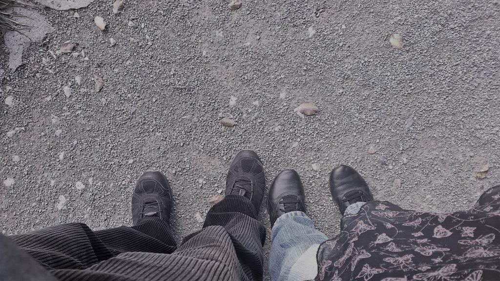 Zwei paar Füße stehen nebeneinander, die eines Mannes und einer Frau.