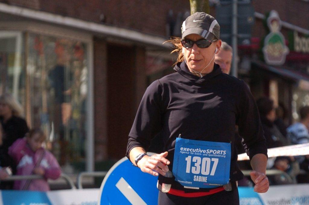 Sabine Scholze mit Baseballkappe und der Nummer 1307 beim Cuxhaven-Halbmarathon, kurz vor dem Ziel. Auch, wenn ich nicht so aussehe: In diesem Moment war Laufen für mich Leben!