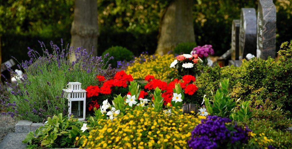 So kann eine Trauerfeier auf dem Friedhof aussehen: Grabschmuck, eine Kerze, viele Blumen.