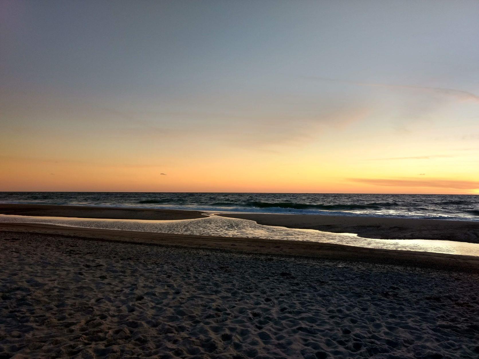 Ein Strand im Sonnenuntergang, im Hintergrund ein zartes Orange, im Vordergrund das Meer - ein weiterer meiner 16 Wünsche