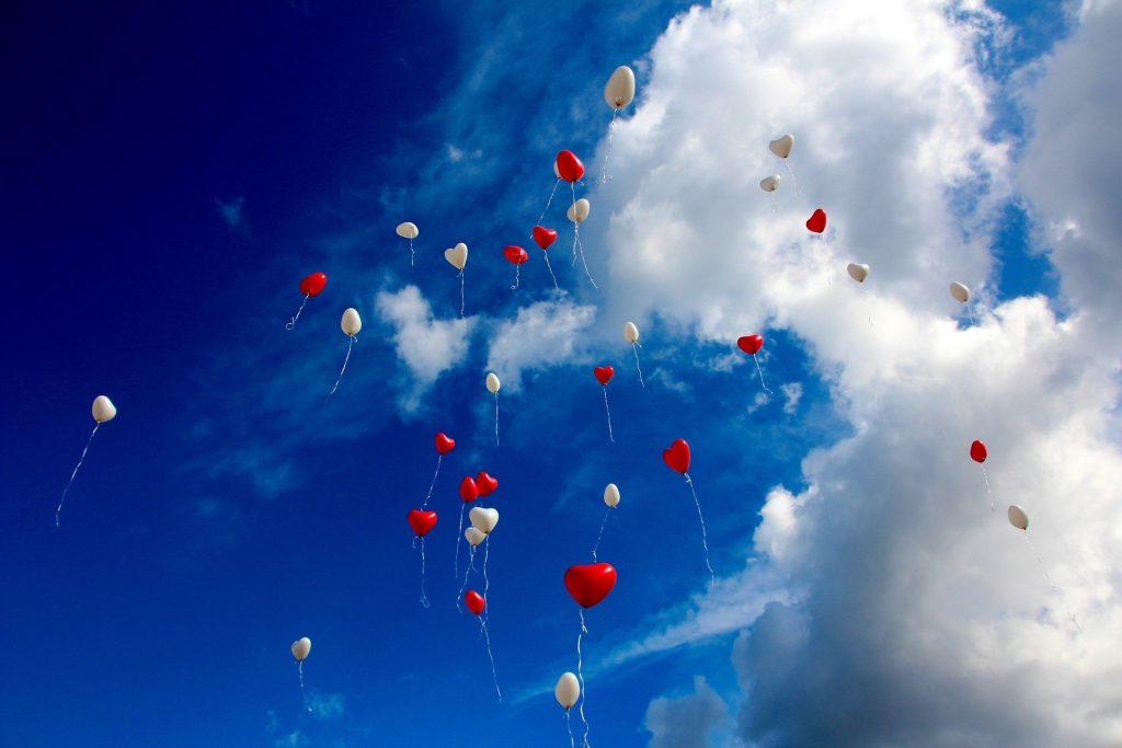 Rote und weiße Ballons in Herzform steigen zu einem blauen, mit einigen Wolken bedeckten Himmel auf - ein Symbol für den inspirierenden Gedanken, dass das Herz ein Ort der Freiheit ist.