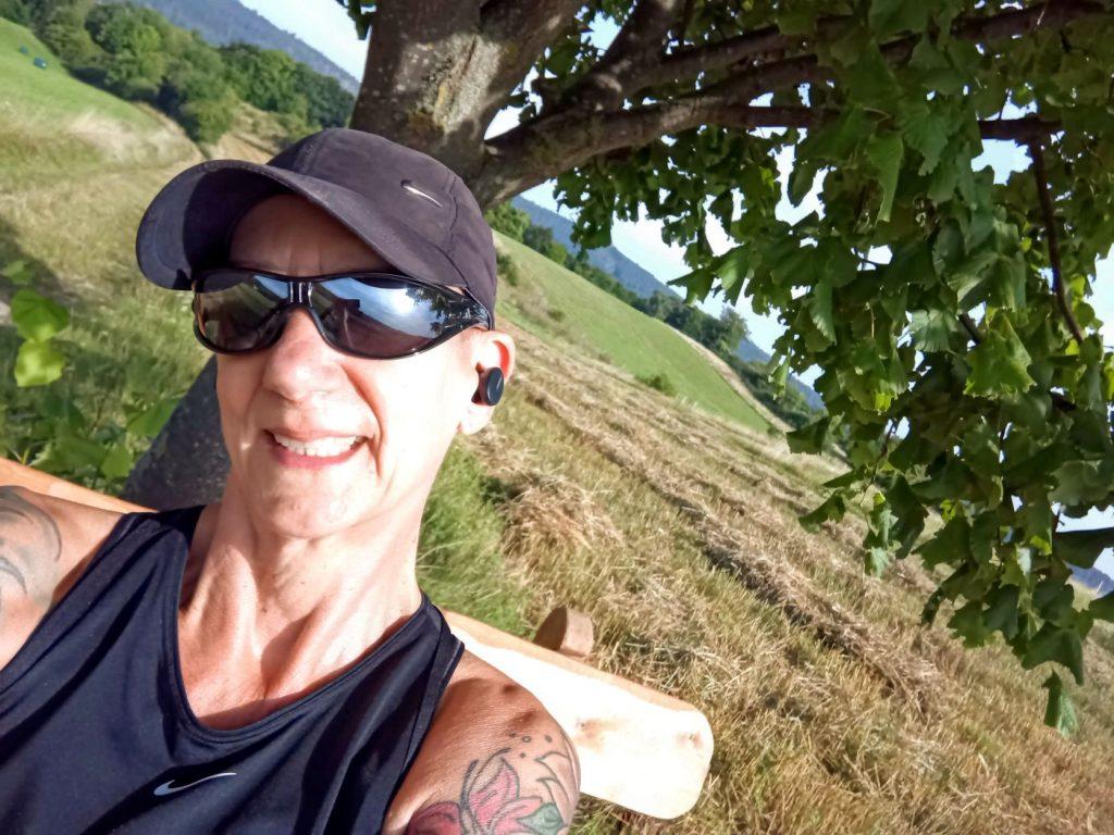 Sabine Scholze sitze auf einer Bank und lächelt, im Hintergrund ein Baum und (abgeerntete) Felder - dies war ein Lauf im Rahmen einer virtuellen Challenge.
