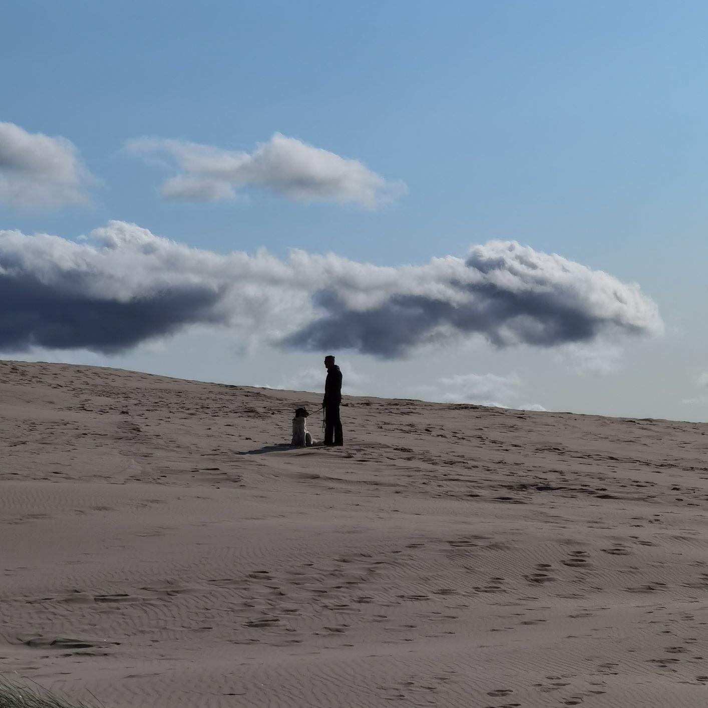 Mein Mann und mein Hund stehen auf einer Düne, im Hintergrund einige Wolken. Einer meiner Wünsche an das Leben ist es, sie genau dort wiederzutreffen.